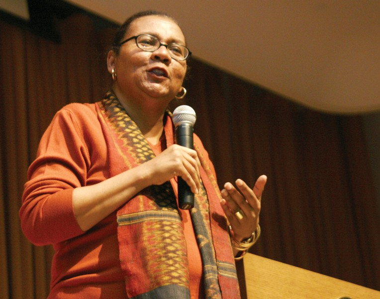 Photo of a black woman in an auditorium, wearing an orange shirt and glasses speaking into a microphone and gesturing.