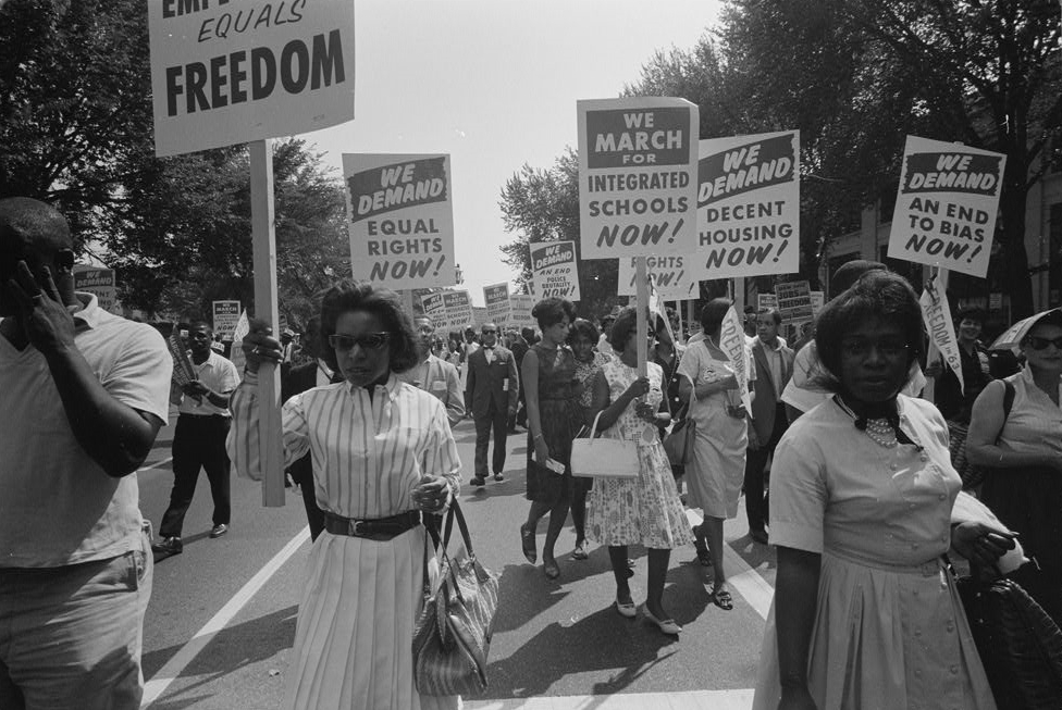 Photo of marchers holding signs demanding equal rights.