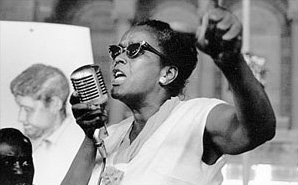 Black and white photo of a black woman speaking passionately into a microphone with her fist raised.