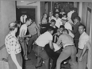 Black and white photo of white men surrounding and attacking a person in a crowded hallway.