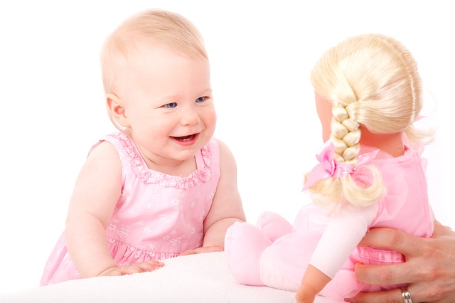 A photograph of a baby in a pink dress smiling at a doll.