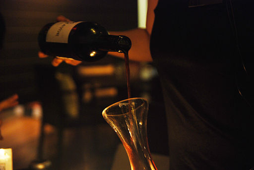 This photo shows wine being poured into a glass container.