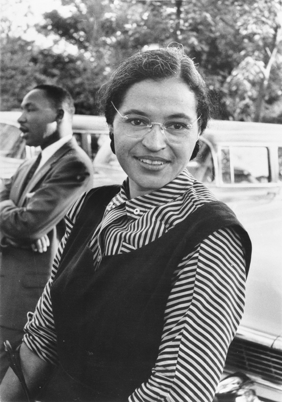Black and white photo of a young smiling black woman (Rosa Parks) with Martin Luther King talking in the background.