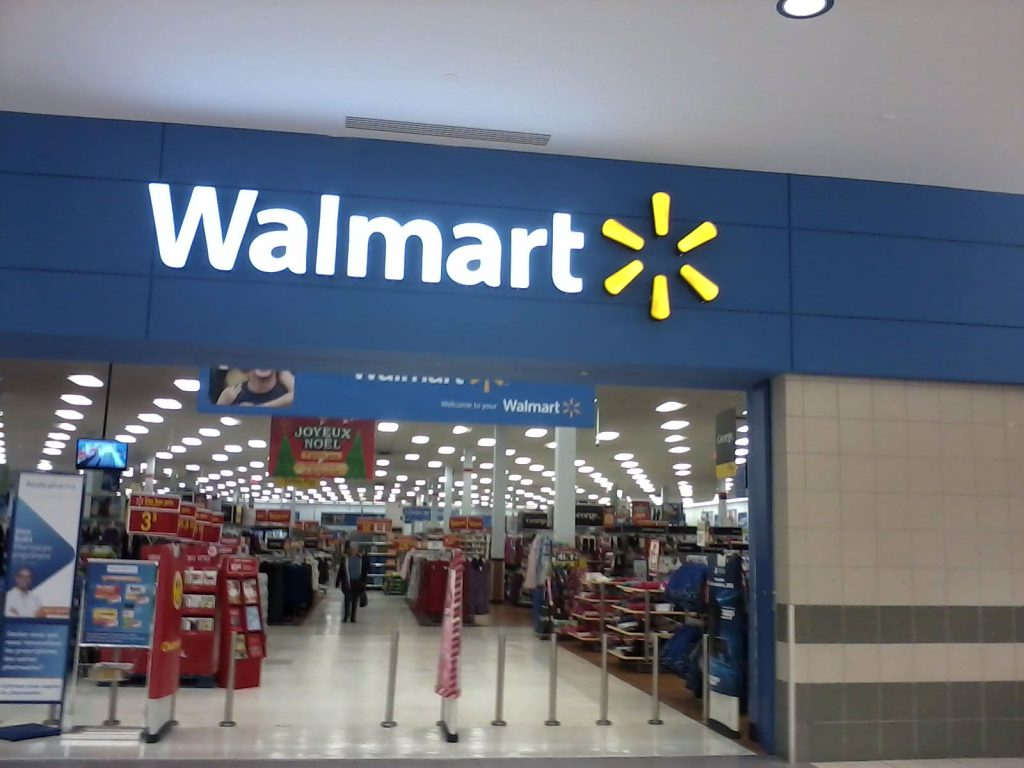 Photo of the entrance to a Walmart store, with a Walmart sign and logo and aisles with products.