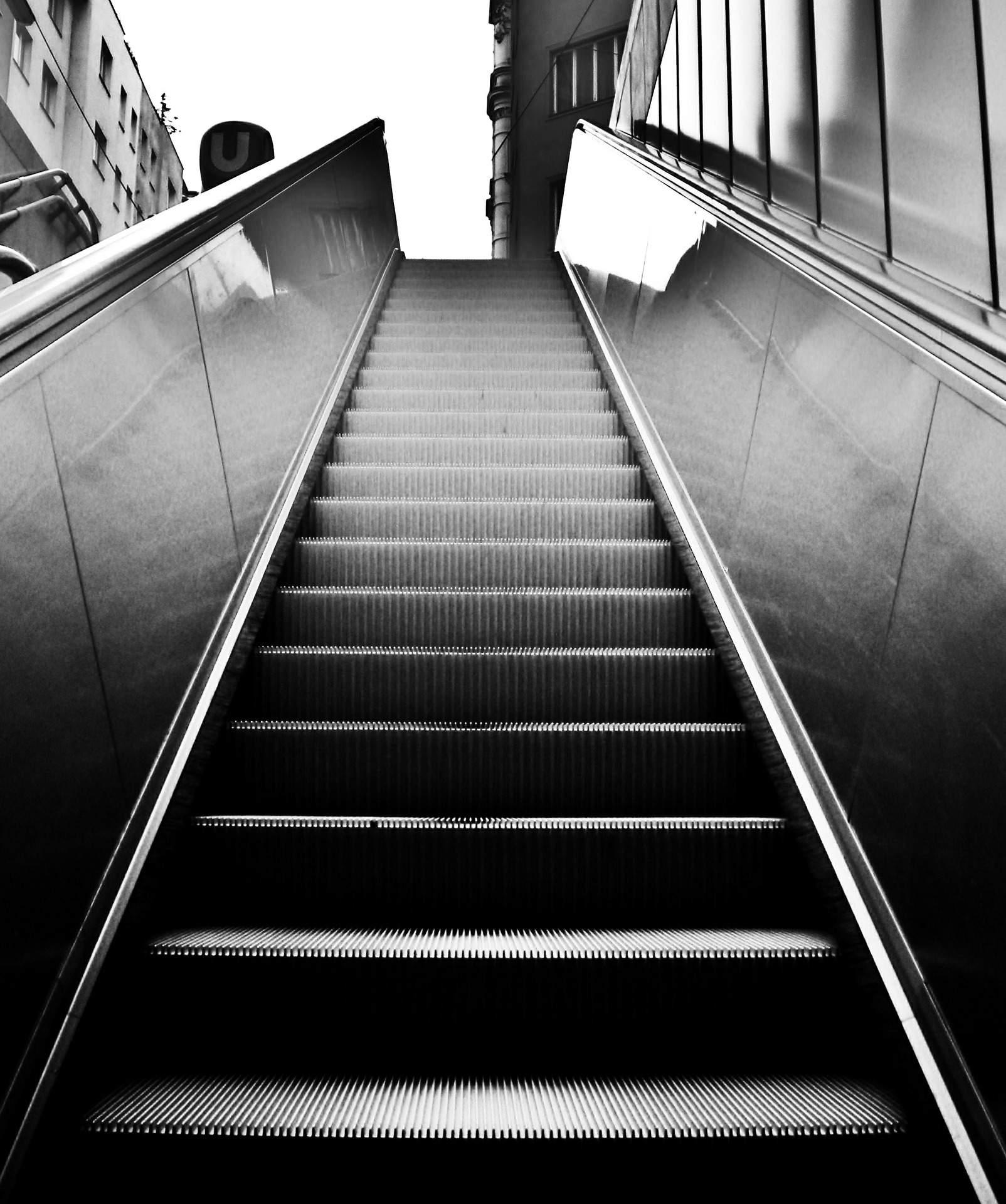A black-and-white photo of an escalator.