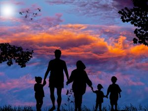 Image of a man, woman, and 3 children holding hands, silhouetted against a sunset with birds flying in the distance.