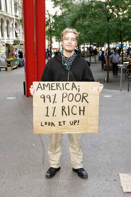 """Photo of a young man holding a protest sign, which reads: """"America: 99% Poor, 1% Rich. Look it up!"""""""