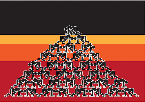Image of people crouching on top of one another to form a pyramid.
