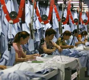 Photo of women working, sewing in a factory.